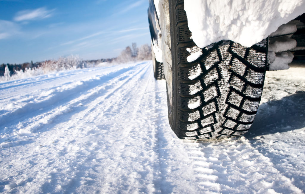 close up of tire driving in winter snow Pride Auto Care Denver Parker Centennial Highlands Ranch